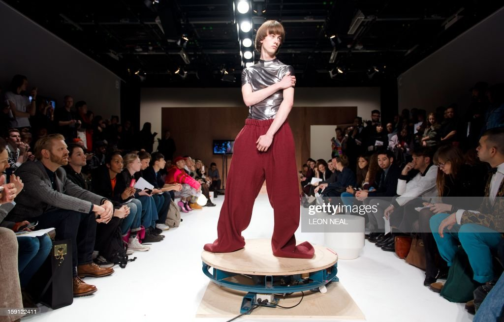 A model stands on a rotating plinth during the Martine Rose presentation at the 'London Collections: Men Autumn/Winter 13' event in central London on January 8, 2013 . AFP PHOTO / LEON NEAL
