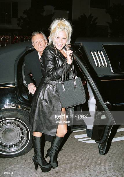 Model Stephanie Heinrich and Playboy founder Hugh Hefner step out of a limousine at Barfly club for the Barfly Friday Night Christmas Party featuring...
