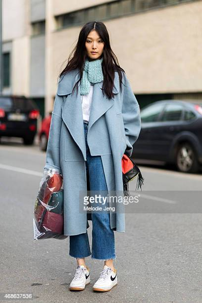 Model SungHee Kim exits the Marco de Vincenzo show in a Tods coat Delphine Delafon bag a scarf she made herself and Nike sneakers on Day 3 of Milan...