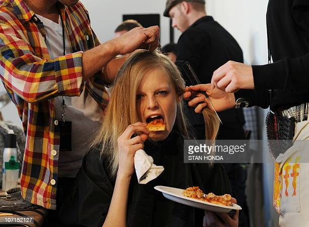 A model takes a bite of pizza while she gets her hair done backstage before the Donna Karan show February 15 2010 during the MercedesBenz Fashion...