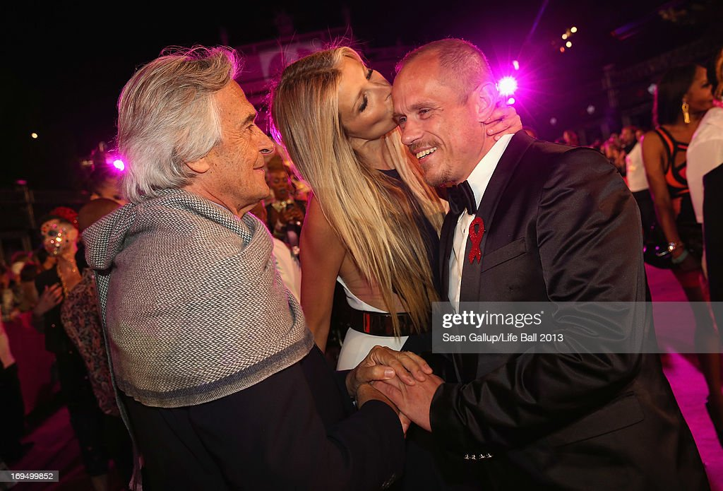 Model Tereza Maxova kisses Gery Keszler as jazz guitarist John McLaughlin looks on on the Magenta Carpet at the 2013 Life Ball at City Hall on May 25, 2013 in Vienna, Austria.
