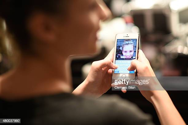 A model texting on her mobile is seen backstage ahead of the 'Designer for Tomorrow' by Peek Cloppenburg and Fashion ID show during the MercedesBenz...