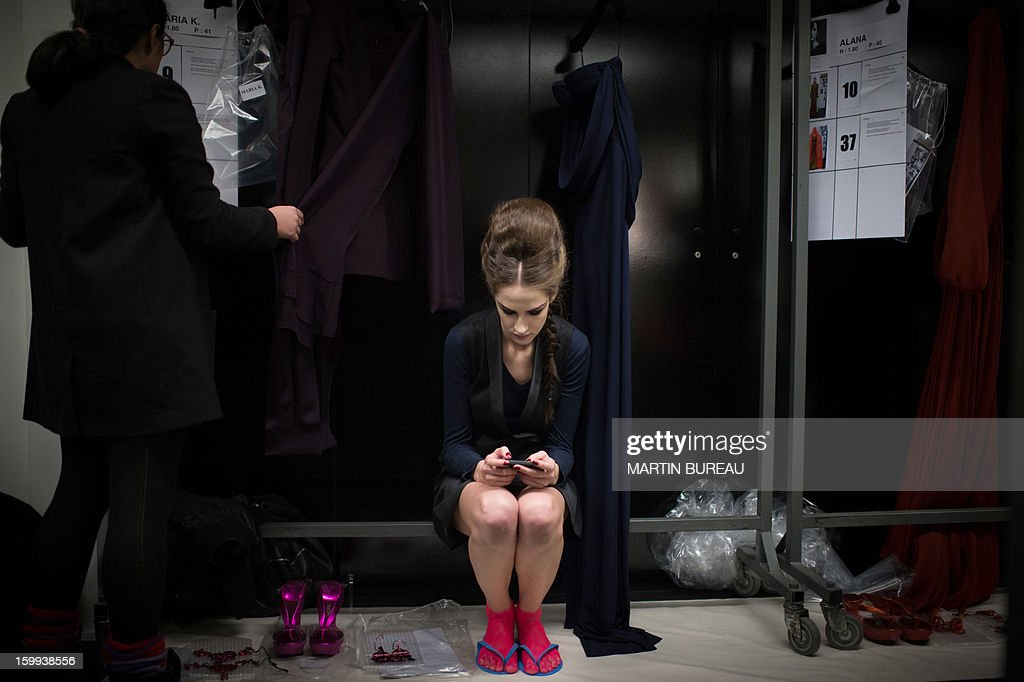 A model texts messages on her mobile phone backstage ahead of French designer Jean Paul Gaultier's show during the Haute Couture Spring-Summer 2013 collection shows on January 23, 2013 in Paris. AFP PHOTO / MARTIN BUREAU