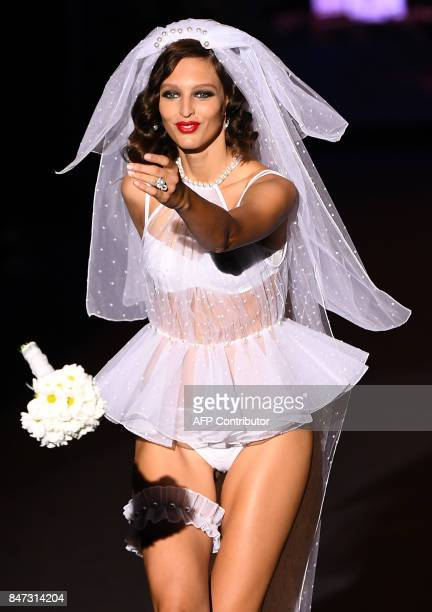 A model throws a bouquet as she presents a bridal gown of Andres Sarda's Spring/Summer 2018 collection during the Madrid Fashion Week in Madrid on...