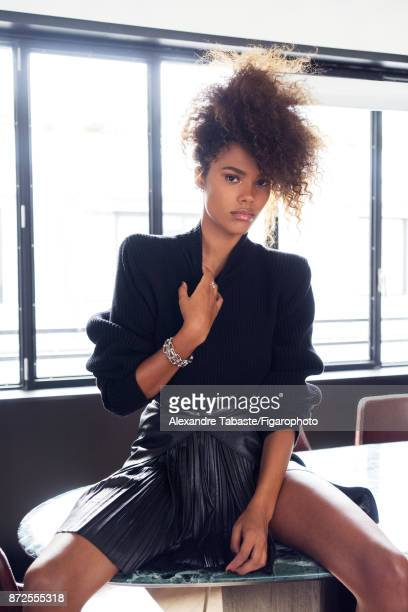 Model Tina Kunakey are photographed for Madame Figaro on September 11 2017 in Paris France Sweater and skirt earrings personal rings bracelets...
