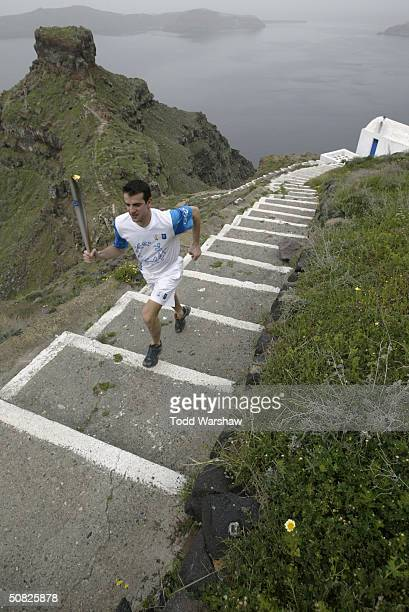 A model torchbearer carries a replica of the Olympic Flame on March 27 2004 around the Greek island of Santorini