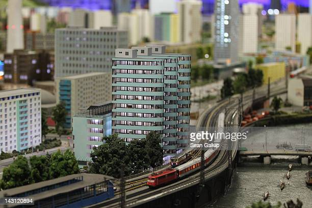 Model trains drive past miniature versions of apartment buildings and the Spree river in east Berlin at the LOXX miniature train landscape at the...
