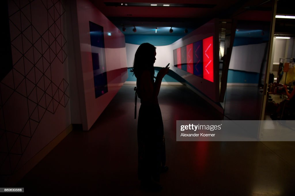 A model types a message on her mobile phone during the American Women's Club And Esmod Charity Fashion Show at DRIVE. Volkswagen Group Forum on October 12, 2017 in Berlin, Germany.