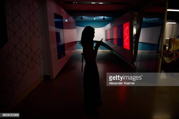 A model types a message on her mobile phone during the American Women's Club And Esmod Charity Fashion Show at DRIVE Volkswagen Group Forum on...