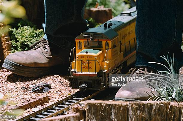 A model Union Pacific freight engine passes between the boots of track maintainer Gerry Boguse June 21 2000 at the Chicago Botanic Gardens in Glencoe...