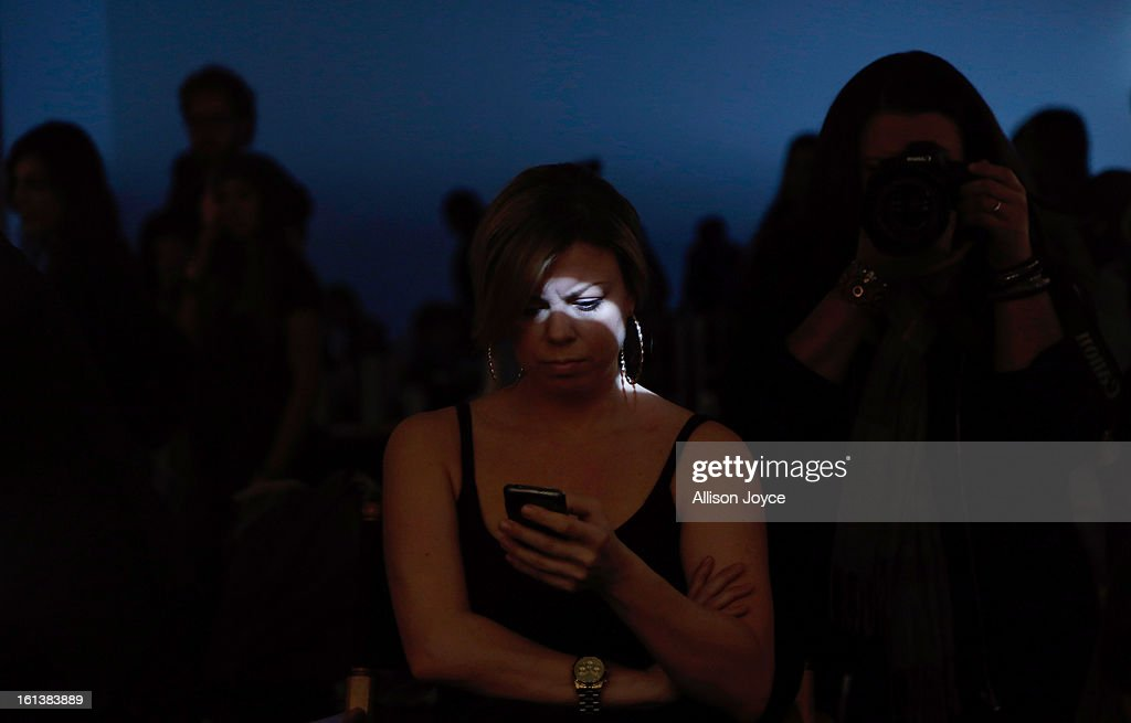 A model uses a smartphone backstage at the Jeremy Laing fall 2013 fashion show during Mercedes-Benz Fashion Week at Pier 59 on February 10, 2013 in New York City.