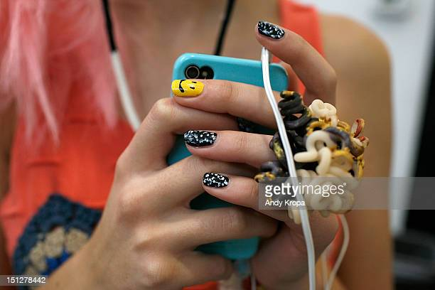 A model uses an iPhone backstage before the Degen spring 2013 presentation during MercedesBenz Fashion Week at Industria Superstudio on September 5...