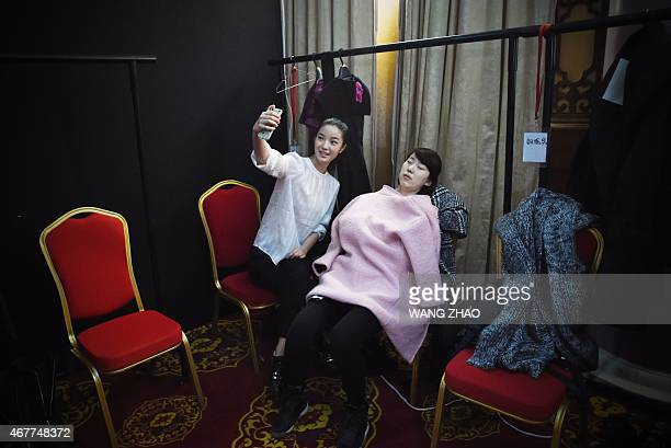 A model uses her mobile phone to take a photograph with a sleeping design team staff member while backstage before the araisara Sara Arai Collection...