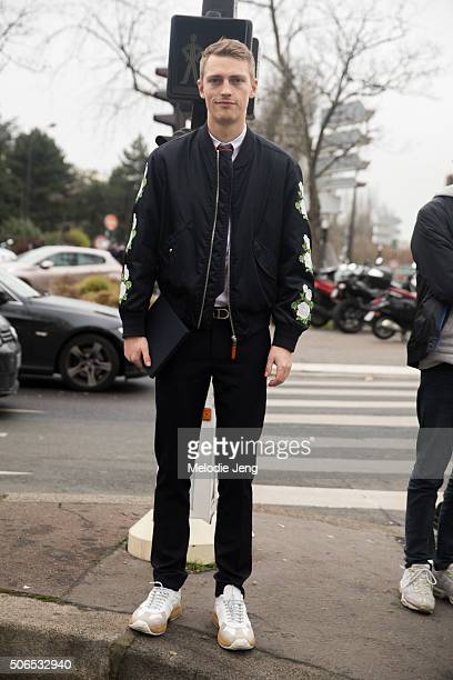 Model Victor Nylander attends the Dior Homme show in a black bomber jacket with florals on the sleeves on January 23 2016 in Paris France