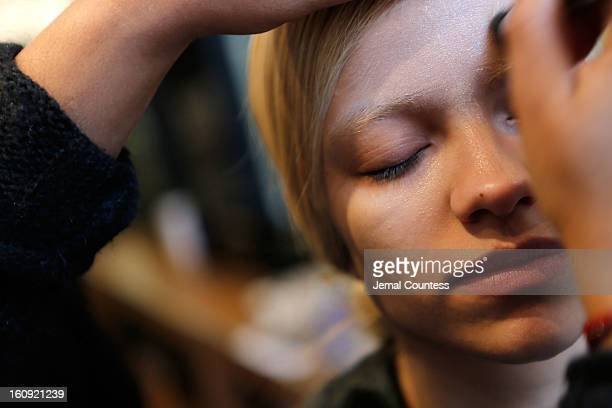Model 'Victoria' is prepped backstage by MAC makeup artist Fatima Thomas at the Haus Alkire fall 2013 presentation during MercedesBenz Fashion Week...