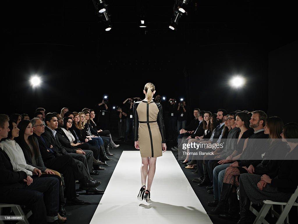 Model walking down catwalk during fashion show : Stock Photo