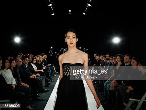 Model walking in foreground on catwalk