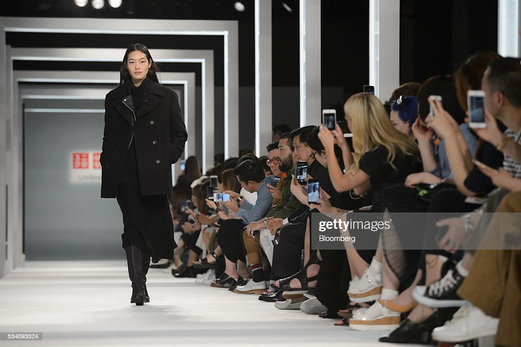 A model walks down the runway as attendees take photographs with their smartphones during a preview of Fast Retailing Co.'s Uniqlo 2016 Fall-Winter lineup in Tokyo, Japan, on Wednesday, May 25, 2016. Analysts and investors will be watching as Uniqlo unveils the new season's LifeWear line in Tokyo to see whether Chairman Tadashi Yanai will come through with his pledge to offer the 'lowest possible prices.' Photographer: Akio Kon/Bloomberg via Getty Images