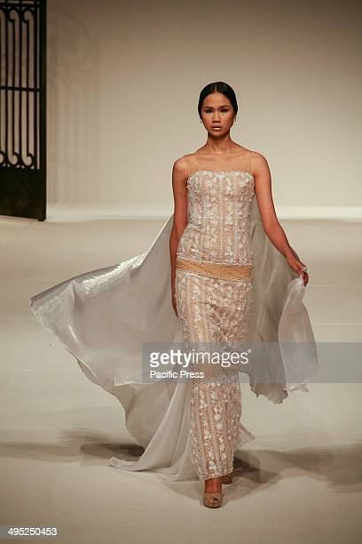 A model walks down the runway wearing one of Albert Andrada's creation during the Philippine Fashion Week Holiday Season fashion show at the SMX in...