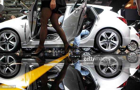 A model walks next a Opel Corsa during the Paris Motor Show on October 04 in Paris France More than a million visitors are expected at the 'Mondial...