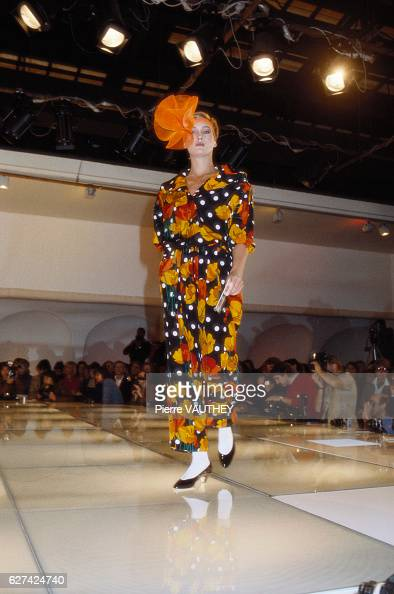 A model walks the runway at the 1982 Pierre Cardin SpringSummer Fashion Show wearing a multicolored haute couture dress and orange hair ornament