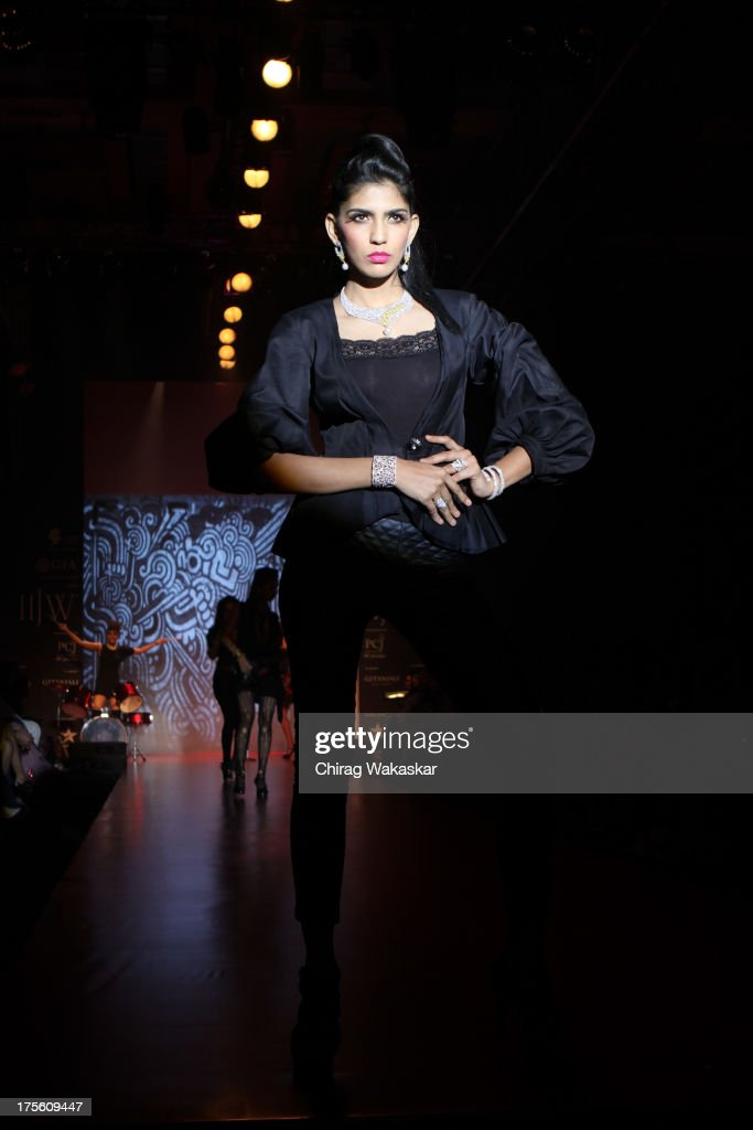A model walks the runway in an Gehna design on day 1 of India International Jewellery Week 2013 at the Hotel Grand Hyatt on August 4, 2013 in Mumbai, India.