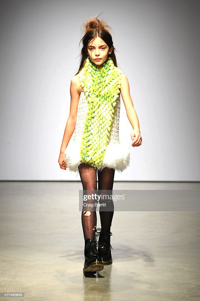 A model walks the runway in fashion by Mischka Aoki at petitePARADE Kids Fashion Week on March 8, 2014 in New York City.