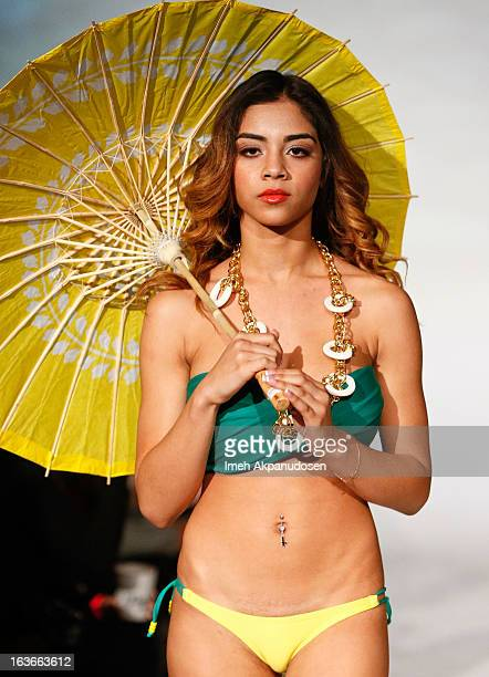 A model walks the runway showcasing designs by Sassi By Nancy E at the Spring 2013 Swimsuit Collection fashion show as part of Los Angeles Fashion...