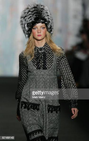 A model walks the runway wearing a black and white herringbone wool with black venise trim jumper and a lace trim blouse at the Anna Sui Fall 2005...