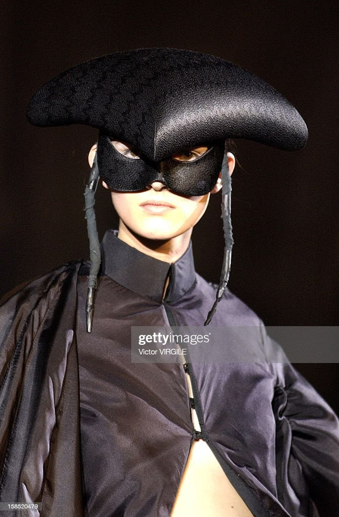 A model walks the runway wearing an ensemble of black parachute silk trousers and a satin hat from Alexander McQueen's fall winter 2002/2003 collection titled 'supercalifragilisticexpialidocious' on March 20, 2002 in Paris, France.