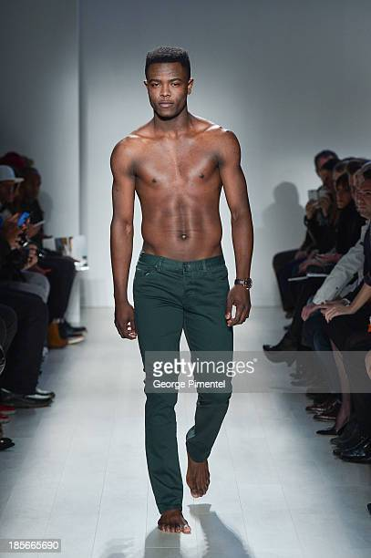 A model walks the runway wearing Triarchy Êspring 2014 collection during World MasterCard Fashion Week Spring 2014 at David Pecaut Square on October...