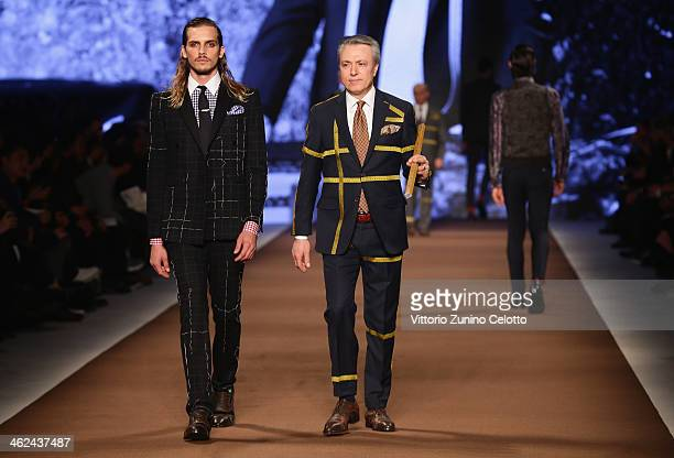 A model walks the runway with a dressmaker during the Etro show as a part of Milan Fashion Week Menswear Autumn/Winter 2014 on January 13 2014 in...