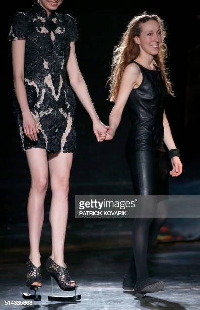 A model walks with fashion designer Iris Van Herpen as she acknowledges the audience at the end of her 20162017 fall/winter readytowear collection on...