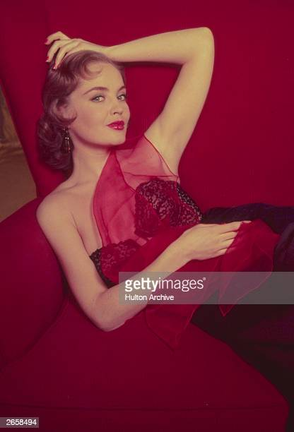 A model wearing a black lace basque reclines in a in a large red armchair