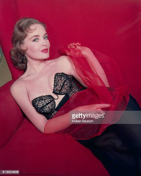 A model wearing a black lace basque reclines in a seat She holds a red chiffon scarf