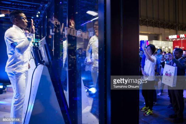 A model wearing a costume of an android character from the Detroit Become Human video game waves in the Sony Interactive Entertainment Inc booth...