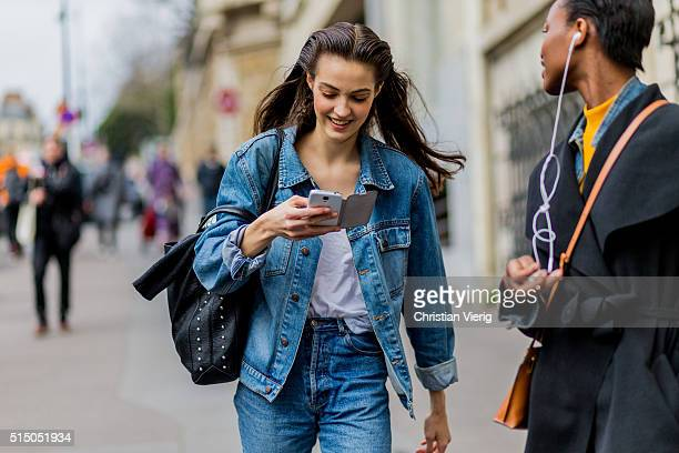 A model wearing a denim jacket outside Miu Miu during the Paris Fashion Week Womenswear Fall/Winter 2016/2017 on March 9 2016 in Paris France