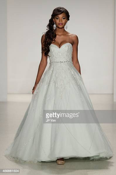 A model wearing a dress inspired by Disney character Tiana from 'The Princess and the Frog' walks the runway wearing Disney Fairy Tale Weddings by...