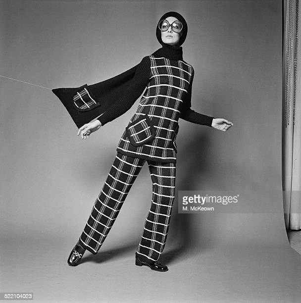 A model wearing a knitted pant suit with long black muffler by MarrianMcDonnell 1969