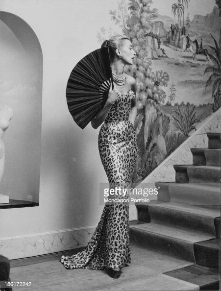 A model wearing a leopard speck evening dress with black satin fan by the fashion house Balmain established by French fashion designer Pierre Balmain...