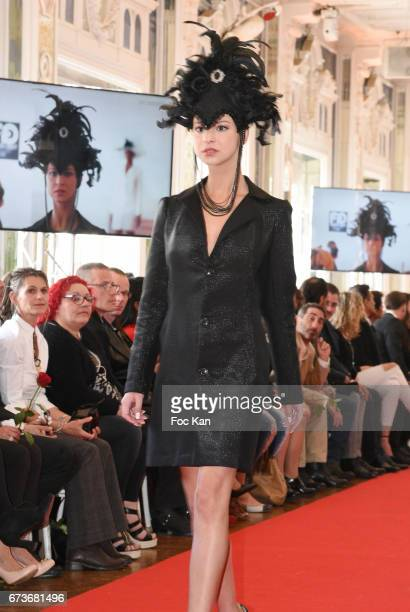 A model wearing a Mira Belle hat walks the runway during 'Fashion Night Couture 2017' Show at Salon des Miroirs on April 26 2017 in Paris France