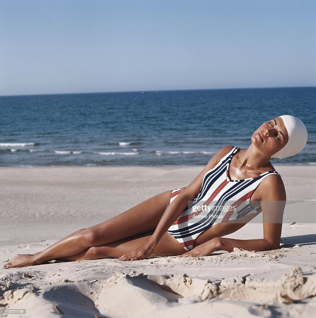 A model wearing a striped cutaway swimsuit reclines on the beach, circa 1973.