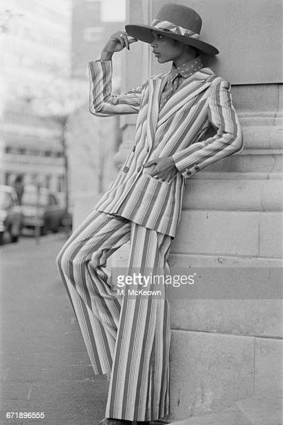 A model wearing a striped trouser suit with a doublebreasted jacket and widebrimmed hat UK 3rd November 1971