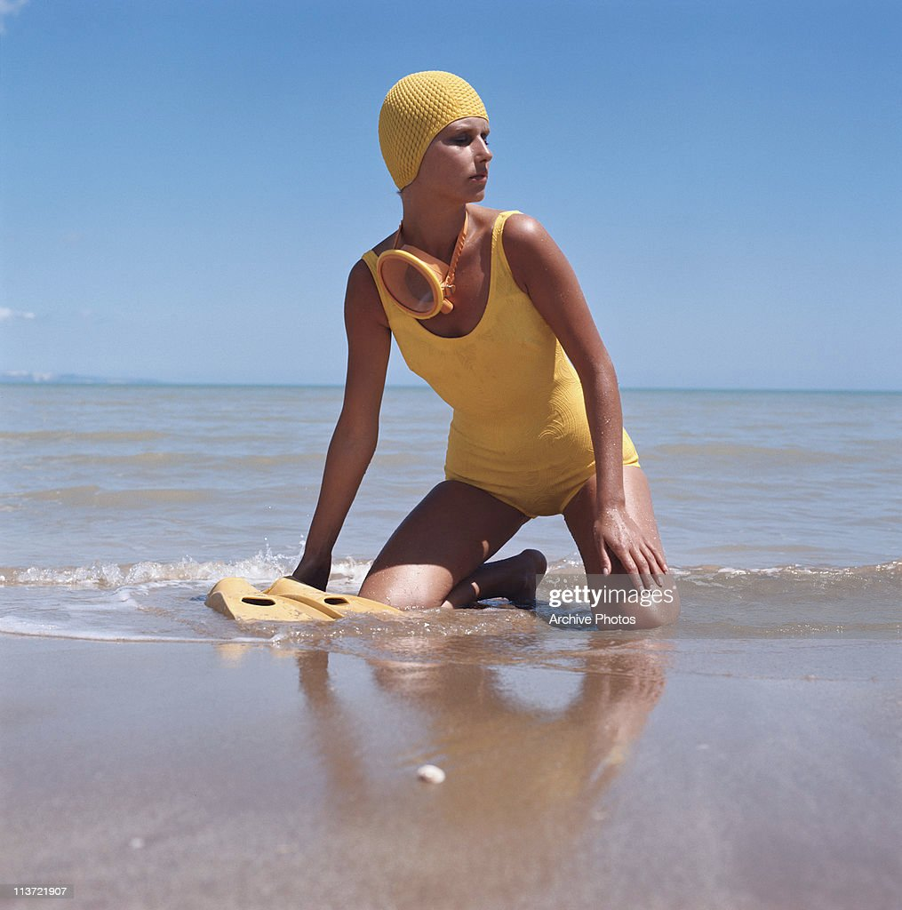 A model wearing a yellow swimsuit with matching accessories on the beach, circa 1975.