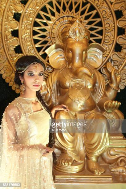 Model wearing an elegant and ornate bridal outfit while posing by a large statue of Lord Ganesh during a South Asian bridal show held in Scarborough...