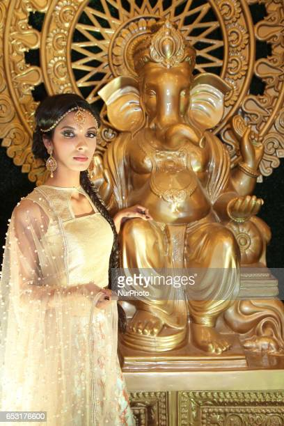 Model wearing an elegant bridal outfit posing by a large statue of Lord Ganesh during a South Asian bridal show held in Scarborough Ontario Canada