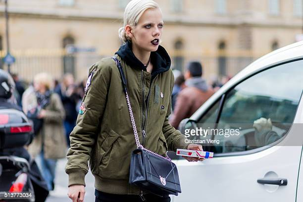 A model wearing an olive bomber jacket and a black Dior bag outside Dior during the Paris Fashion Week Womenswear Fall/Winter 2016/2017 on March 4...