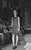Model wearing antlers walks the runway at British fashion designer Alexander McQueen's first New York fashion show at a former synagogue on Norfolk...