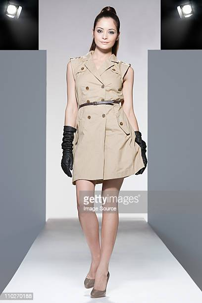 Model wearing beige dress on catwalk at fashion show