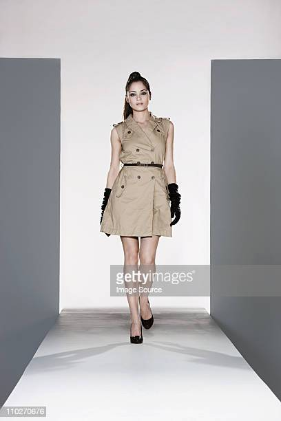 Model wearing beige dress on catwalk at fashion show